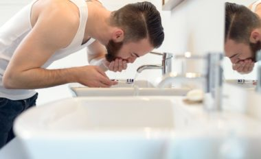 Man rinsing his toothbrush under running water from the tap in the hand basin after shaving above his beard to neaten his appearance, side view bending down